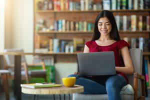 Smiling korean girl using laptop for online work or studies at cafe